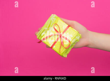 Female hand holding a stack of sanitary pads tied with a red ribbon in her hand, pink background, copy space, critical days, intimate - Stock Photo