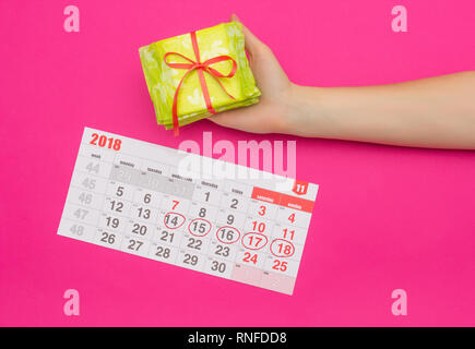 Calendar with marked days of menstruation in a girl, female hand with a stack of sanitary pads, pink background, background, protective - Stock Photo