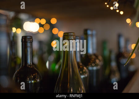 decorative interior elements-dark glass empty bottles on shiny background.Many glass wine bottles as a decor.Bar counter. Decorated with a set of - Stock Photo