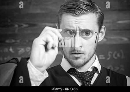 Closeup portrait of blond guy holding glasses with magnifying lenses in front of his eyes. Gentleman with perfect hairstyle, stylish beard and big - Stock Photo