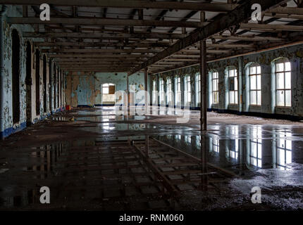 Light from the windows of an old mill reflected in the waterlogged floor - Stock Photo