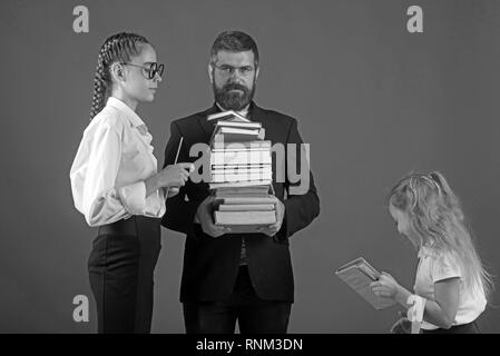Back to school and home schooling. Teacher man and girls hold book pile at school. Literature lesson and reading grammar book. School time of sisters - Stock Photo