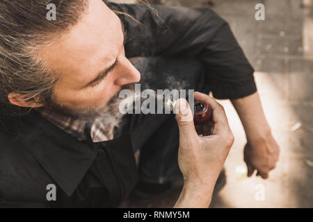 Bearded brutal man smoking pipe in park, close up portrait - Stock Photo