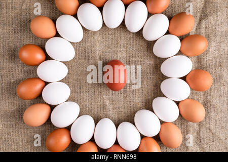 White and brown eggs are lying in circle with one red egg in center on canvas. - Stock Photo