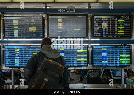 Young man checking the Arrival and Departure gate listings at Fort Lauderdale-Hollywood International Airport. - Stock Photo