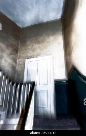 A stylised and atmospheric image of door on the half landing of a spooky staircase in a Victorian house - Stock Photo