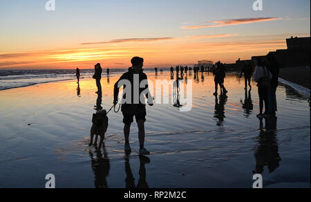 Brighton, UK. 20th Feb, 2019. Visitors enjoy a beautiful sunset on Brighton beach as sunny weather is forecast to continue in the south over the next few days Credit: Simon Dack/Alamy Live News - Stock Photo