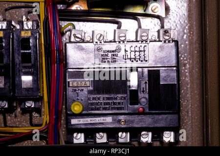 Old 3 phase circuit breaker in electric distribution case. Closeup - Stock Photo
