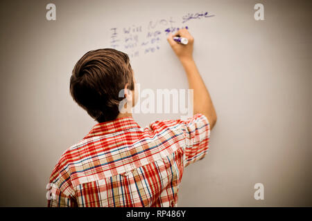 Teenage boy writing lines on a whiteboard. - Stock Photo
