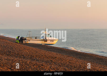 Lone Fisherman Launching Boat from Beach in Aldeburgh on a February Morning - Stock Photo