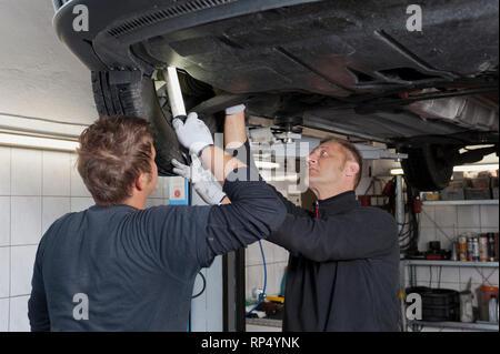 KFZ Teckniker Meister erklaert seinem Lehrling zum KFZ Mechatroniker. In einer kleinen Werkstatt [(c) Dirk A. Friedrich - Stock Photo