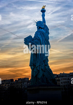 Replica of the Liberty Statue against the sunset in Paris - Stock Photo