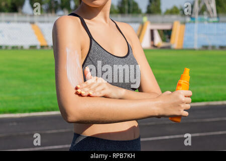 Woman spraying sunscreen cream on skin before run. Sports and healthy concept. - Stock Photo