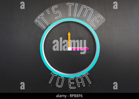 Neon concept clock sign showing 'Eat Time'. Maket clock on black wall indicating time for meal. - Stock Photo
