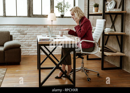 Fit blonde woman on high heels solving business problem throughout call - Stock Photo