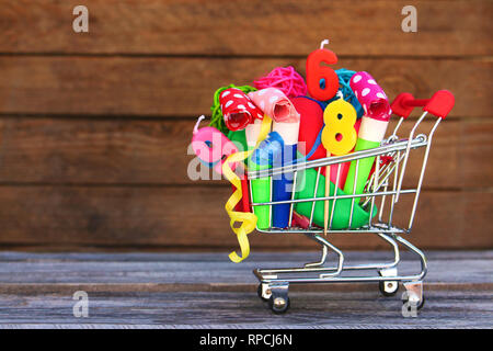 Shopping cart with items for birthday celebration on wooden background. - Stock Photo