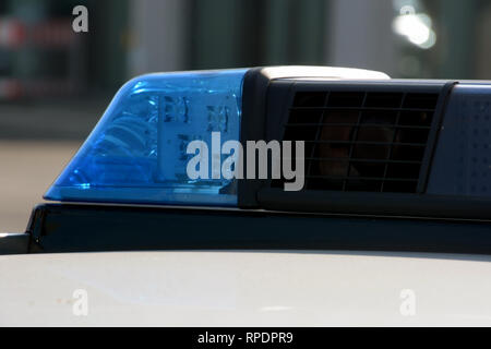 blue light flasher on a top of a german police car by day, german police lights on a car - Stock Photo