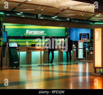 HAMBURG, GERMANY - MAR 20, 2018: Customers at europcar desk at Hamburg airport terminal - Stock Photo