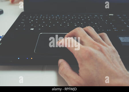 Man's hand using black laptop touchpad, trackpad use, drag and drop, gestures, keypad - Stock Photo