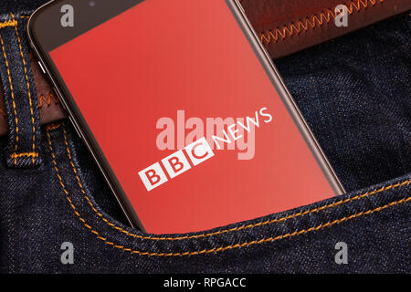 Black phone with red logo of news media BBC News on the screen. News media icon. Denim jeans background - Stock Photo