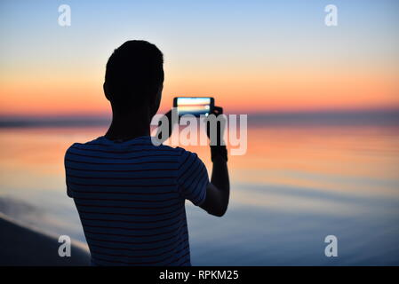 Silhouette of young guy taking a photo of a beautiful orange sunset over the Baltic sea with mobile phone camera. Summer morning. Dawn. - Stock Photo