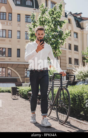 Full-length portrait of businessman standing on the pathway of a park with his bicycle while going to office. Handsome brown-haired man dressed in a white shirt and jeans commuting to office on a bike standing in a park with his bicycle and using his phone. Casual wear - Stock Photo