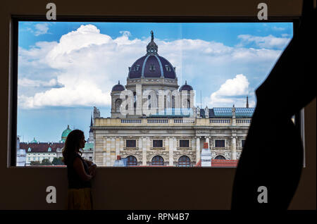 Young woman admiring the view of the Kunsthistorisches museum from a window inside Leopold Museum, Vienna, Austria - Stock Photo