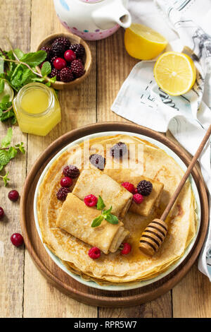 Healthy Pancakes breakfast. Stack of homemade thin pancakes or crepes on a rustic table, served with honey and fresh berries. - Stock Photo