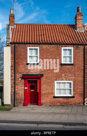 English Village Red Brick detached house with Red Door in Market Place, Tickhill in the Metropolitan Borough of Doncaster in South Yorkshire, England, - Stock Photo
