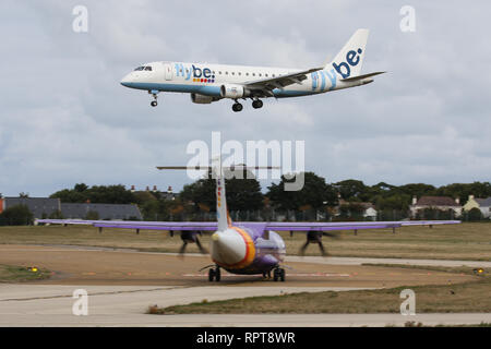 An Embraer 175, operated by FlyBE, passes an ATR 72-500, operated by Blue Islands in FlyBE colours as it lands at Jersey Airport - Stock Photo