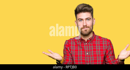 Young handsome man clueless and confused expression with arms and hands raised. Doubt concept. - Stock Photo