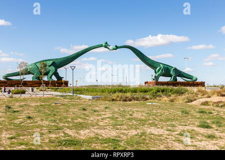Erenhot, Inner Mongolia, China - September 23, 2018: Two green kissing dinosaurs. Statues of two dinosaurs located on both sides of the road near the  - Stock Photo