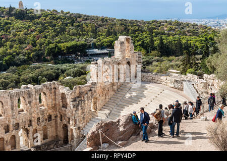 Athens, Greece - November 1, 2017: Tourists visit the Odeon of Herodes Atticus, an ancient stone theatre structure located on the southwest slope of t - Stock Photo
