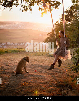Pretty young girl on a swing during amazing sunset. A dog sits near the girl. Wind blowing her hair. Slow motion - Stock Photo