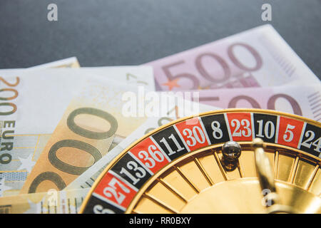 Gold casino theme. Image of casino roulette, poker games, money on the table, all on a dark bokeh background. Place for printing and logo. - Stock Photo