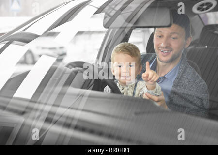 Front view through windshield of father and son sitting in driver's seat of automobile and observing car cabin. Little cute boy looking at camera, pointing with finger. - Stock Photo