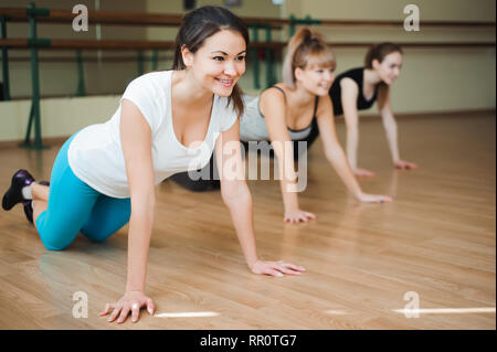 Group women on floor of sports gym doing push ups. Fitness club - Stock Photo