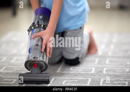 child using a vacuum cleaner while cleaning the carpet in the house - Stock Photo