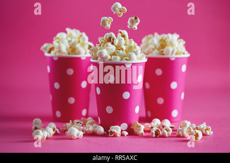 Tasty popcorn falling into cups on pink background. Salty fresh crusty homemade popcorn in pink paper cups. - Stock Photo