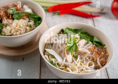 Asian soup noodles with chicken in bowl on wooden table. - Stock Photo