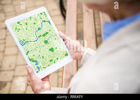 selective focus of senior woman using digital tablet with map on screen - Stock Photo