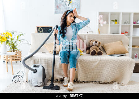 tired african american woman sitting on sofa while holding vacuum cleaner rod - Stock Photo