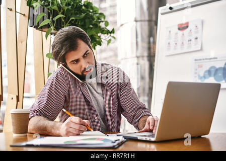 Young serious businessman in casual wear is talking on the phone, while sitting in office in front of laptop, using it, making notes in his notebook. Freelancer analyzes data, develops development strategy. Business education for adults. - Stock Photo