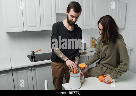 beautiful young couple preparing orange juice during breakfast in kitchen - Stock Photo