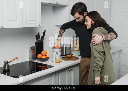 beautiful young couple making orange juice and hugging during breakfast in kitchen - Stock Photo
