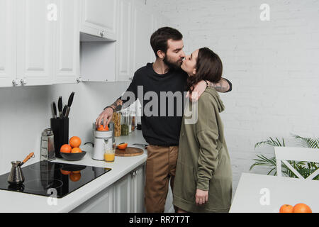beautiful young couple making orange juice, hugging and kissing during breakfast in kitchen - Stock Photo