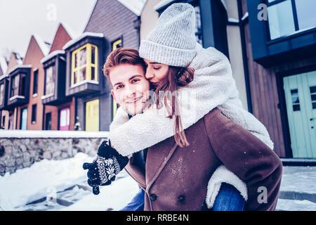 Loving beautiful girlfriend kissing her handsome blue-eyed man - Stock Photo