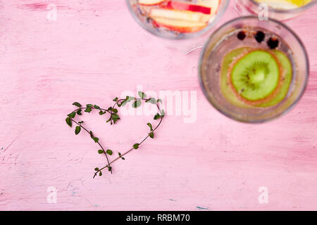 Variety of  Detox infused water with heart from mint on pink background. Refreshing summer homemade cocktail. Diet. Healthy drink. Love. Top view. Cop - Stock Photo