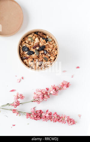 Home made granola cereal flakes with dried fruit, nuts and honey in a craft paper box with dried flowers on white table. - Stock Photo
