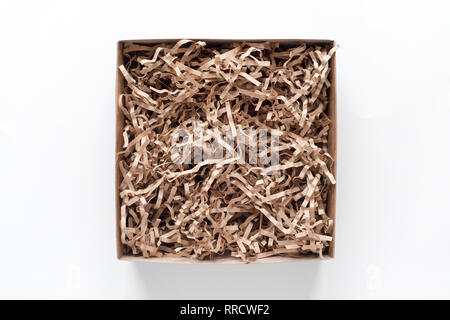 Opened gift box with decorative straws fillers on light background. Brown craft paper box for your product placement or montage. Top view, flat lay - Stock Photo